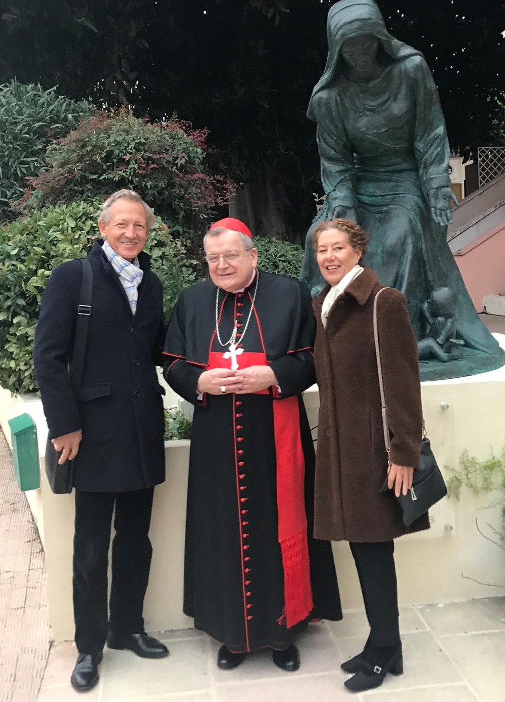 "Adrian Dozier, Cardinal Raymond Burke and Patrizia Salles at the blessing of the ""Notre Dame of Innocents"" in front of the statues. Nun leaning slightly forward with the unborn babies at her feet."
