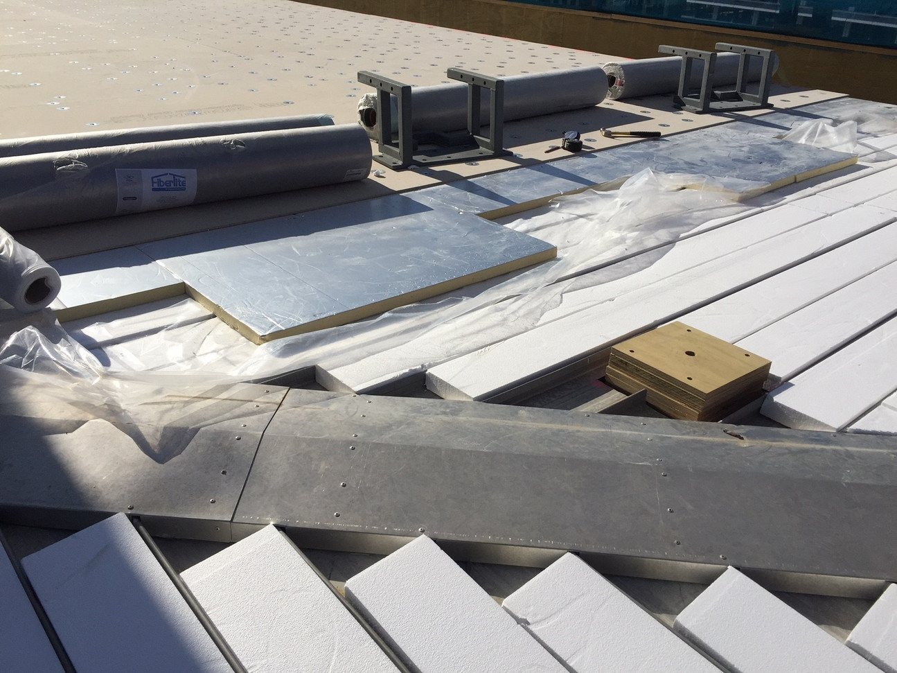 Polystyrene infills to existing trough section roofing as part of membrane overlay