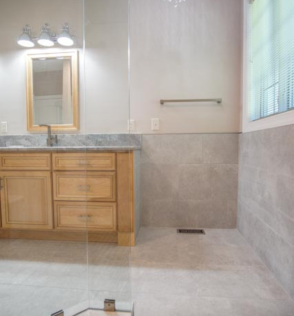 Bath remodel with a curbless shower entry and frameless enclosure