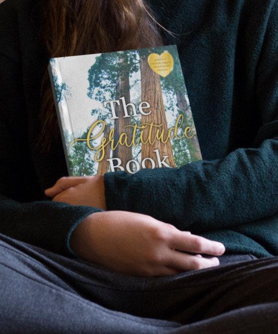 little-girl-holding-a-book-mockup-sittin