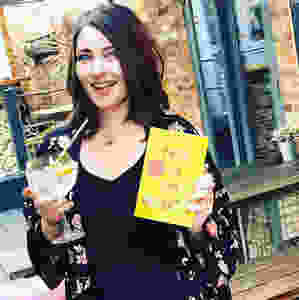 Katy Colins author of How To Say Goodbye holding book and drink