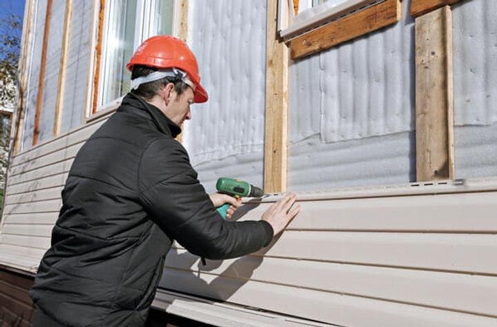 bigstock-A-Worker-Installs-Panels-Beige-