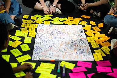 There is a big piece of white paper on a black floor. On the piece of paper there is writing in loads of different coloured pens, the word consent is written in a circle in the middle of the paper. There are yellow and pink post it notes with writing on, around the paper.