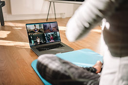 View of a woman conducting virtual fitness class with group of people at home on a video c