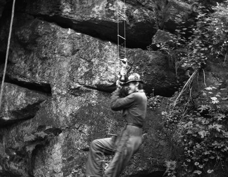 Bari Logan in traditional caving gear practising on the new ladders. Limestone crags, near Matlock.