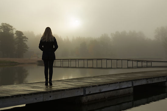 Young woman standing alone on lake footb
