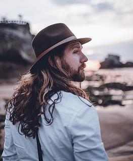 Il s'agit d'un portrait de Dylan Boiteux, au bord du plage, le regard contemplant l'horizon.