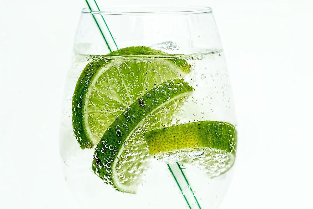 Glas mit prickelndem Mineralwasser und Limetten.