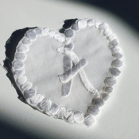 a white heart with an embroidered initial