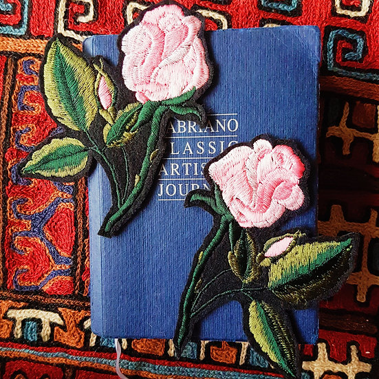 2 pink embroidered rose stem patches on top of a blue book