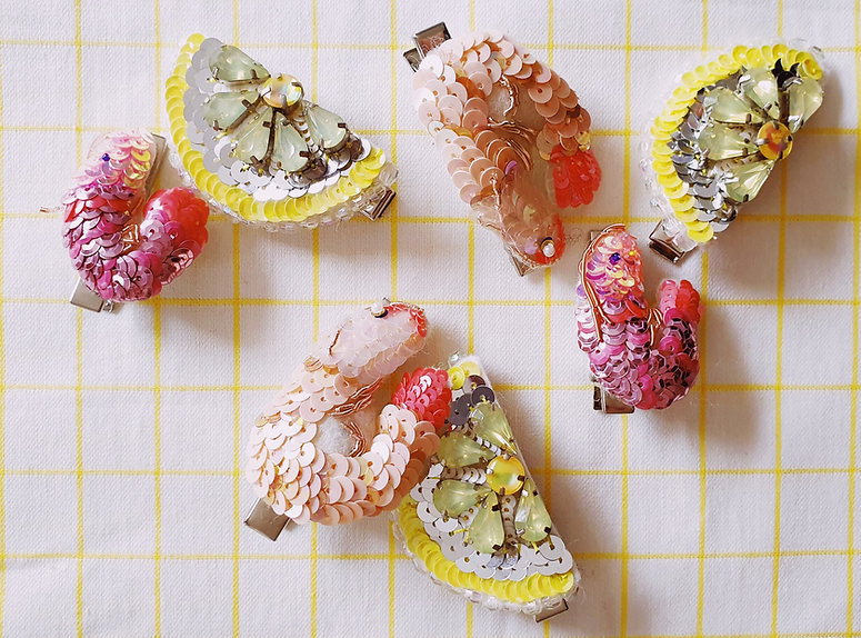 A collection of sequinned shrimp and lemon slice hair clips on a yellow and white check background