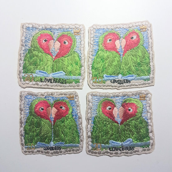 A group of 4 embroidered stamps with 2 lovebirds on