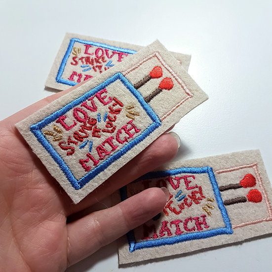 A hand holding an embroidered matchbox patch
