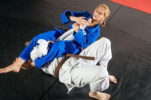 Judo, Jiu Jitsu. Two women are fighting on tatami. Blue and white kimano. Painful receptio