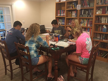 Julia Ross tutoring four teenage students in math, SAT & ACT, at the Professional Tutoring Cottage.