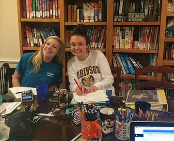Tutoring Students working on math at the Professional Tutoring Cottage in front of bookshelves.