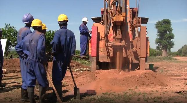 men drilling borehole.png