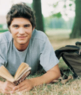 Young man lying on grass reading.