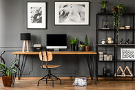 Posters on grey wall above wooden desk i