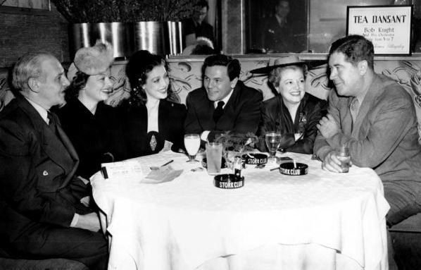 Winchell, far left, holding court at The Stork Club.