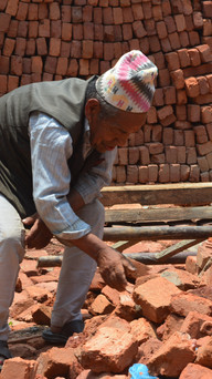 old man finds a brick in the rubble, to rebuild his home with