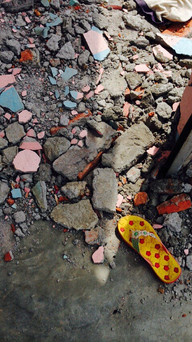 child's slipper left in the remains of her home, at the epicenter
