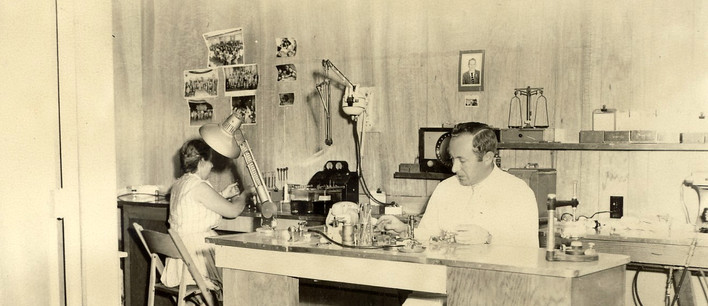 Jacob Birnbaum working in his lab, with his wife Mira in the background