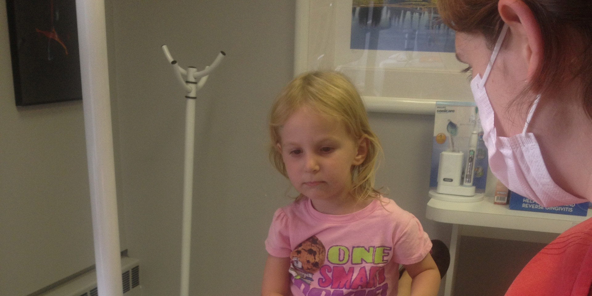 Dr. Heidi's daugher Abby around age 2, watching her grandmother Robin having her teeth cleaned