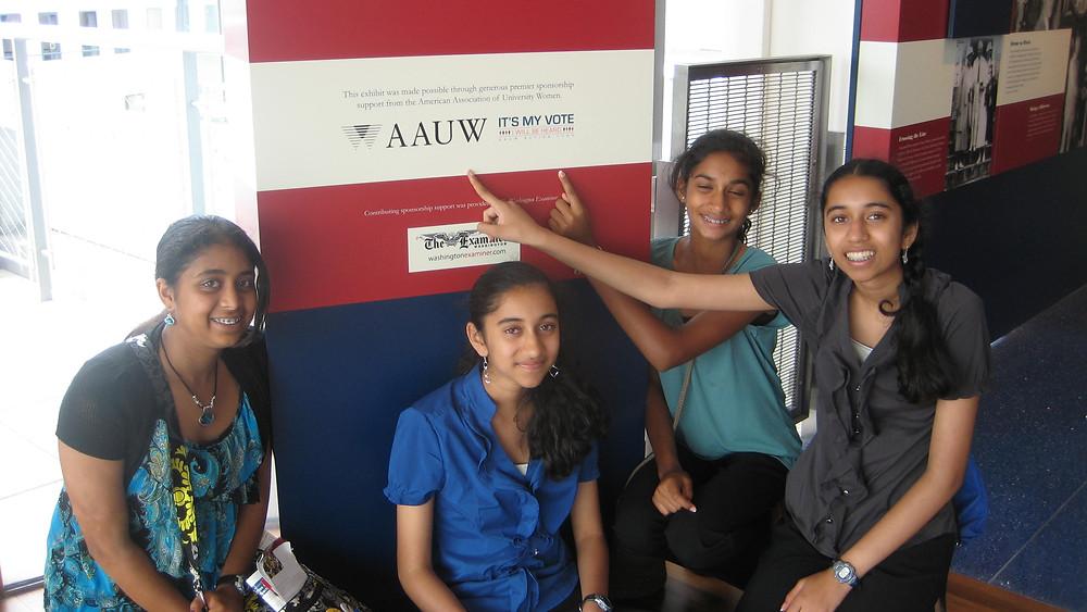 Maanasa Nathan, Priya Ramamoorthy, Smrithi Mahadevan and Kavya Ramamoorthy pointing to sign - AAUW It's my vote @ Newseum