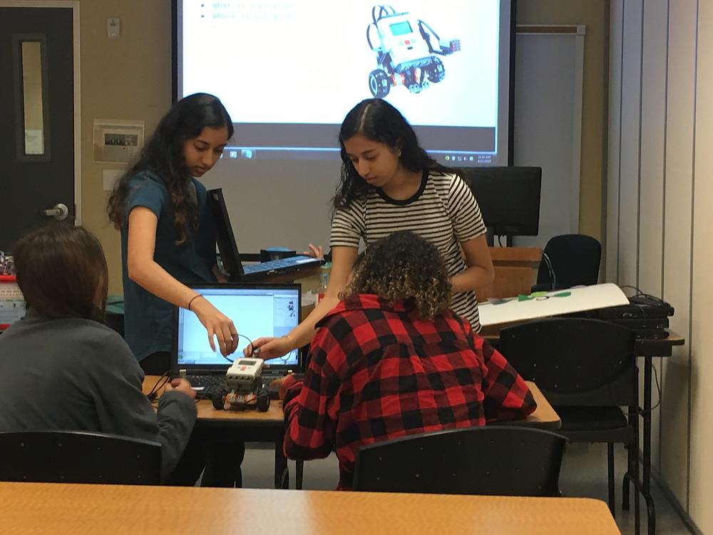 Priya Ramamoorthy and Kavya Ramamoorthy teaching how to program the robot