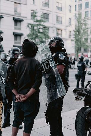 Police in riot gear confront peaceful protestors.