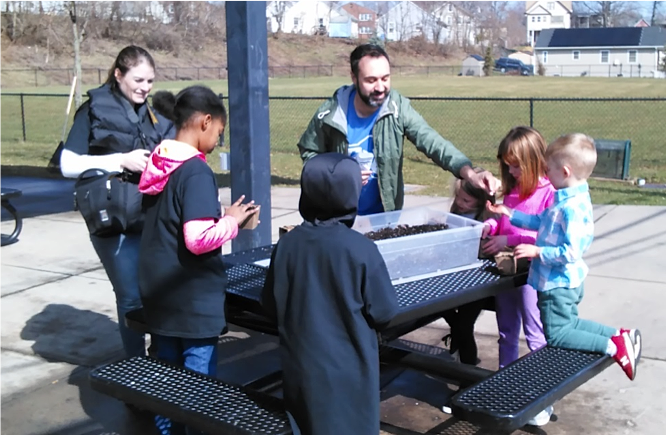 Joey Listro, Executive Director of New Britain Roots, helps children plant seeds at the Spark the Park Clean Up at Willow St. Park in April 2019