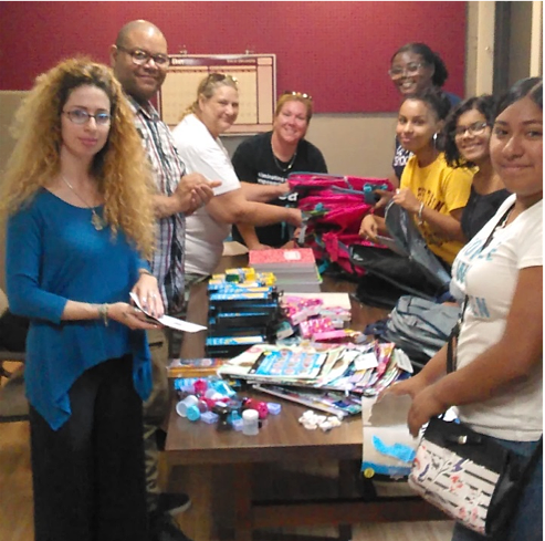 Resident leaders, YW staff and teens stuff backpacks donated by Walmart and YWCA New Britain following youth party attended by 120 teens