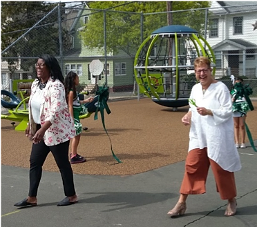 Northend School Principal Talisha Foy and New Britain Schools' Superintendent Nancy Sarra cheer on the students on their first day of play on the playscape.