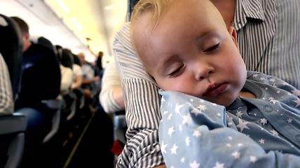 baby op schoot bij moeder in vliegtuig.j