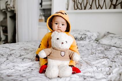Baby sitzen auf Bett mit Teddybär