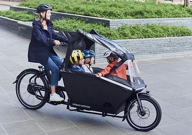 Vrouw met 3 kinderen fietst op urban arr