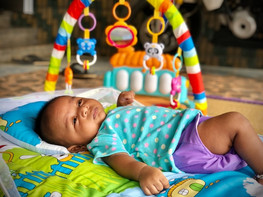 Donkere baby liggend op speelkleed.jpg