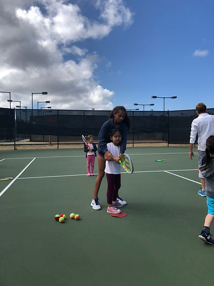 Charity Co-Founder helps underserved young girl learn how to play tennis.