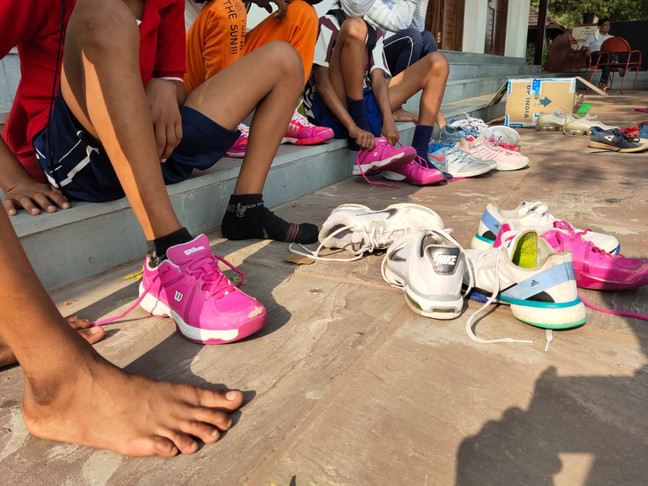 Indian children playing sports with used athletic shoes