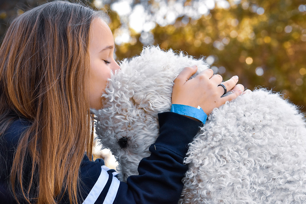 Beautiful Teen kissing her fluffy white dog