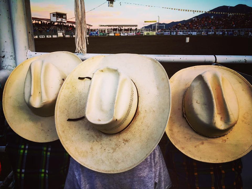 Three young boys watch the rodeo intently keeping their championship dreams alive.