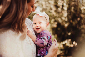 baby girl snuggles mom during spring family photos by carmel indiana photographer