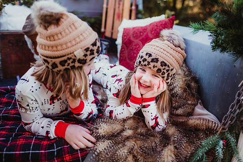sisters wearing beanies in old truck during noblesville christmas mini sessions for holiday cards 2021