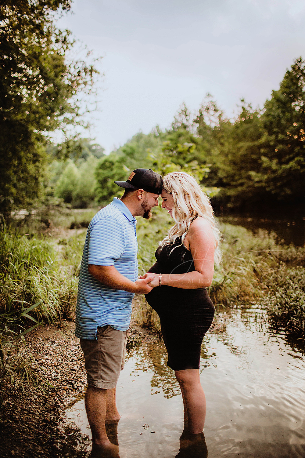Maternity Outfits, pregnant woman holding hands with husband, river bank session in noblesville, indiana with newborn photographer
