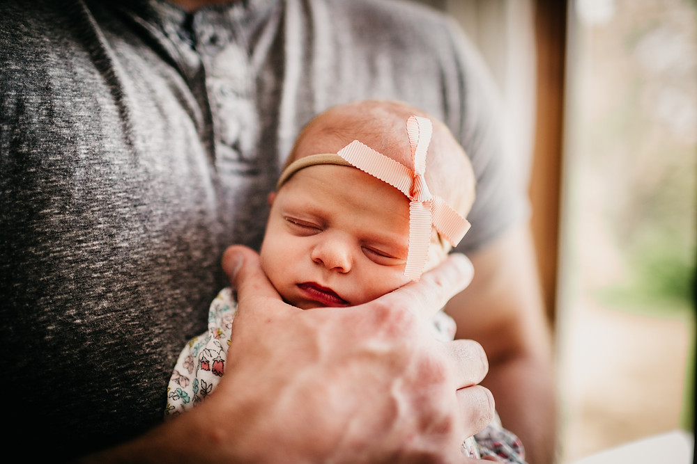 newborn in pink bow held by dad, Anderson Photographer, Lifestyle Newborn Photography