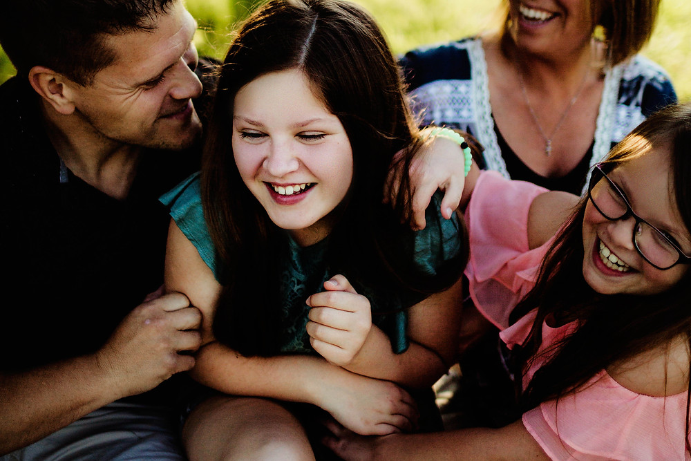 tween girl laughing with sister and family during family photography session in carmel indiana