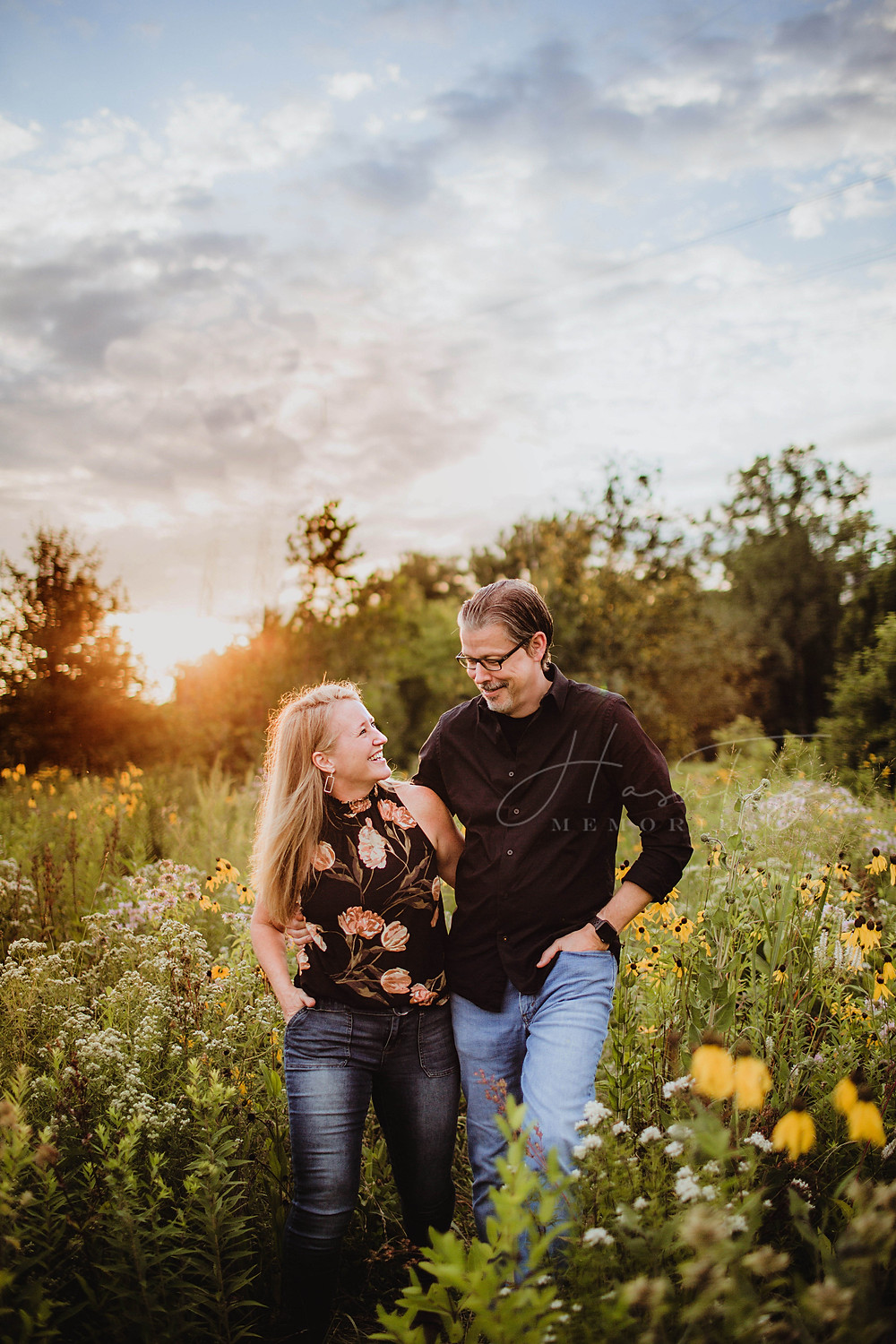 couple laugh in flower field during summer family photo shoot