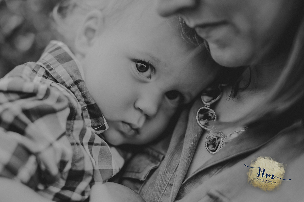 mommy snuggles of toddler at family photo shoot at Tuttle Orchards