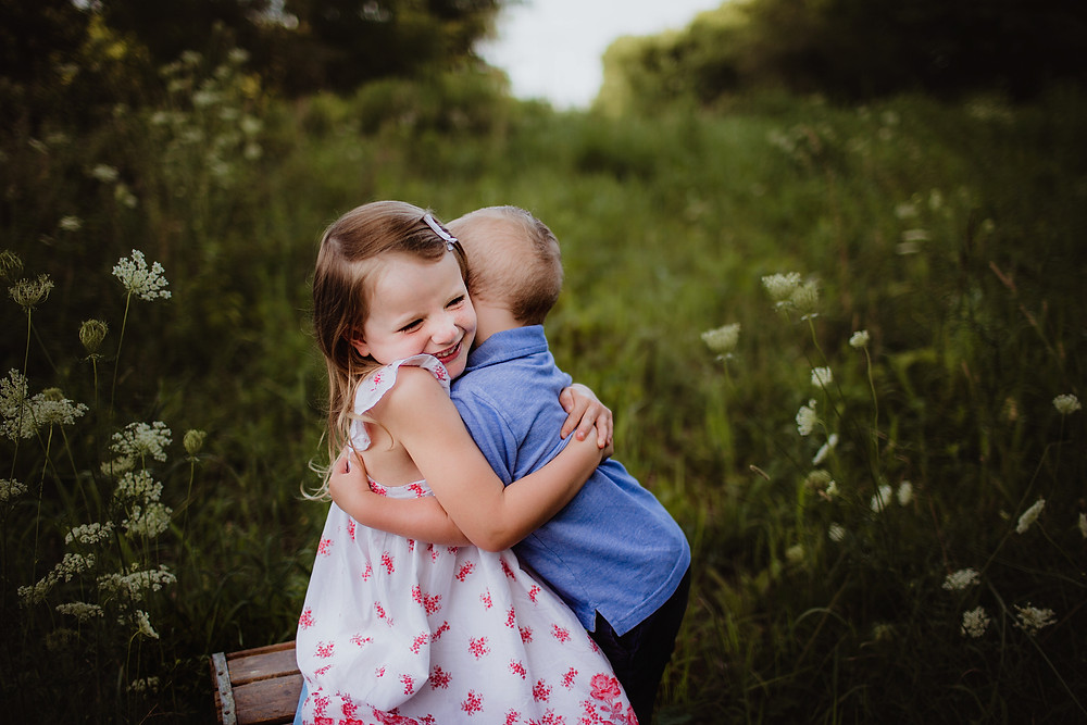 brother and sister hugging in family photography outfits, midwest field photography by Hashtag Memories Photography